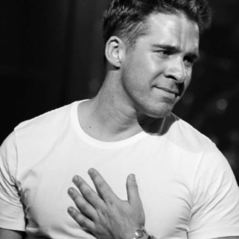 Swing a Ding Den - A black and white photo of Hugh Sheridan wearing a white t-shirt with one hand on his chest.