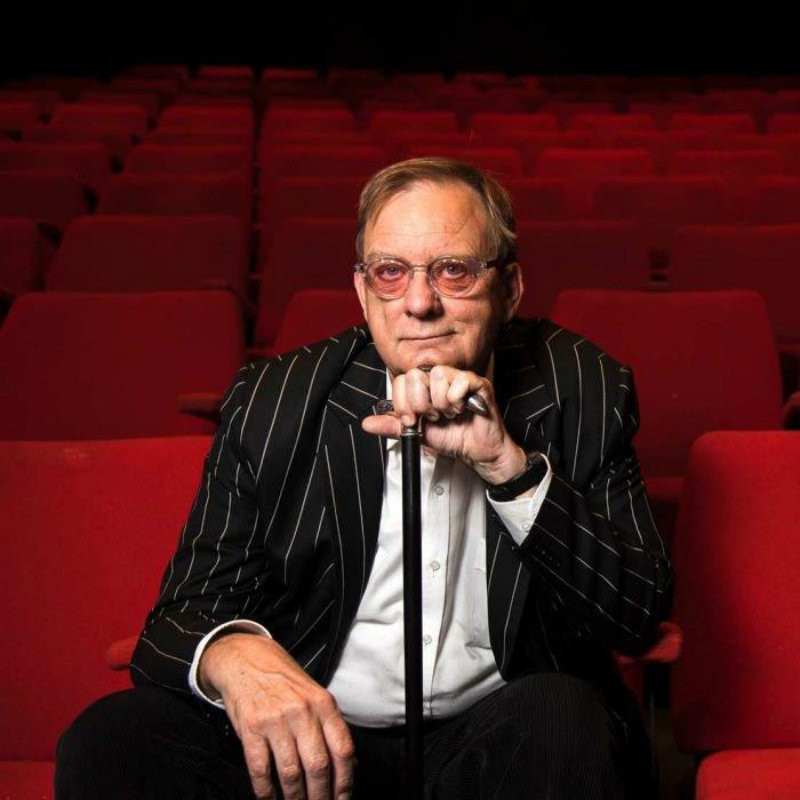 Peter Goers in Joyful Strains - A photo of a man resting his head on a walking stick. He is wearing a black and white striped jacket, white shirt and rose tinted glasses. He is sitting in an empty theatre that has rows of red fabric chairs.