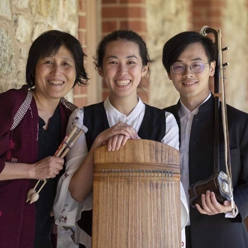 A photo of three people smiling holding oriental wooden musical instruments.
