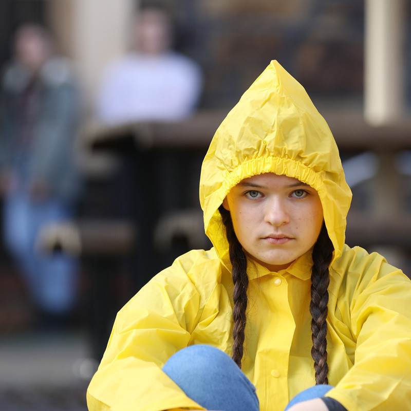 Very Happy Children With Bright and Wonderful Futures - A young girl with long plaits is sitting cross legged on the ground. She is wearing a bright yellow rain coat with the hood up.