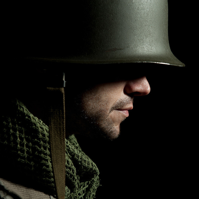 A Soldiers Secret - A side profile photo of a man wearing a khaki helmet and scarf. The background is black and there is a shadow casted over his eyes so only his nose and mouth are visible.