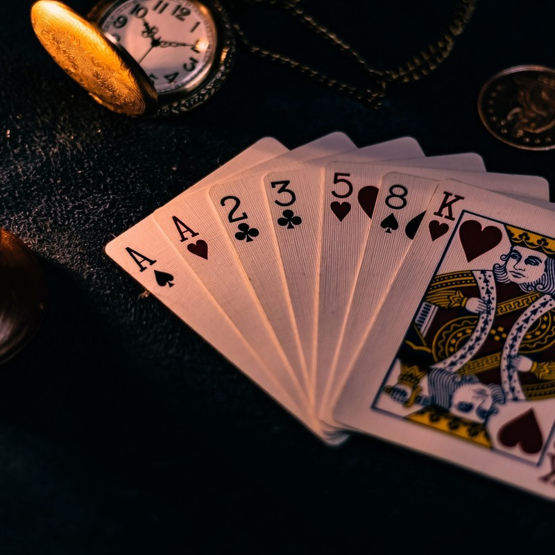 Magic For You - A close up image of seven playing cards fanned on a black table along with a gold watch face.