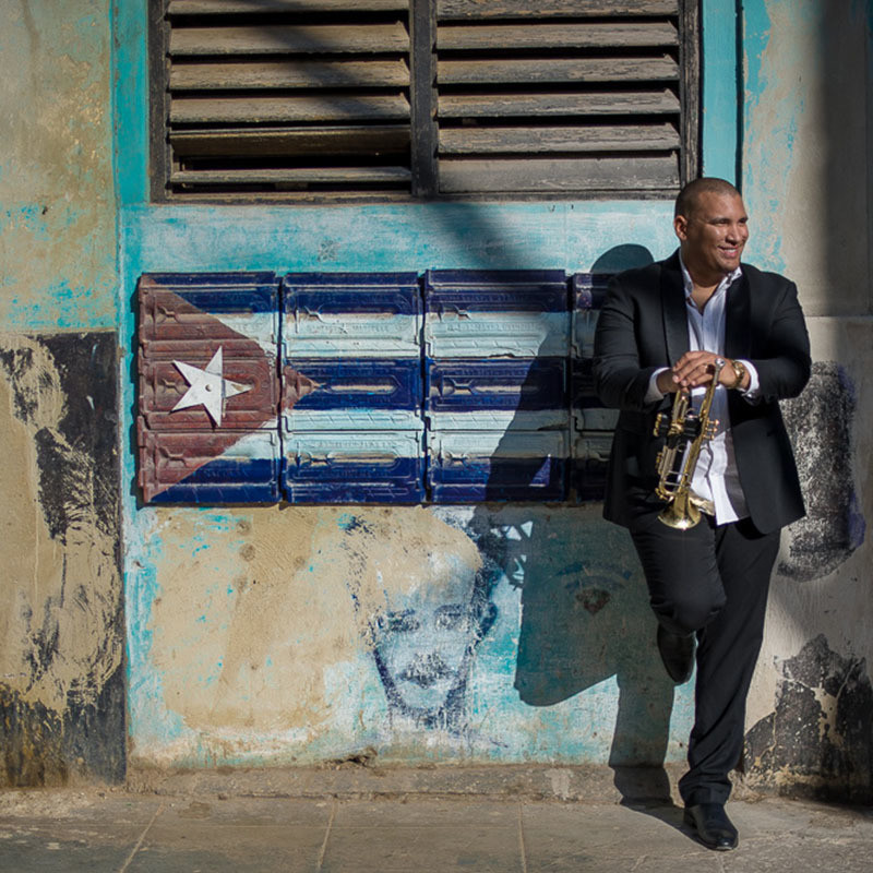 A photo of a man leaning against a wall. He is wearing a black jacket, black pants and white shirt. He is holding a gold trumpet. The wall is painted with the Cuban flag which features a red triangle with a white star within it, and three horizontal blue stripes and 2 horizontal white stripes.