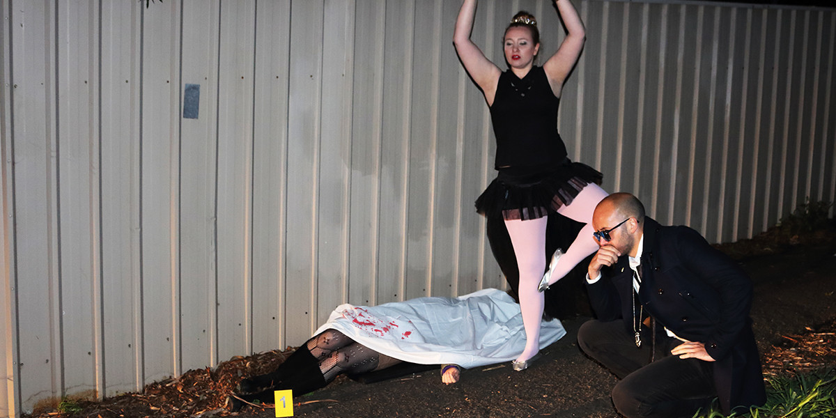 A photo of a woman dressed as a ballerina and a man dressed as a detective standing around a body on the ground covered by a white sheet.