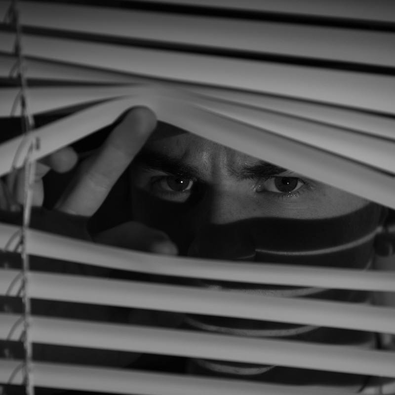 A black and white photo of a person peering through venetian blinds.