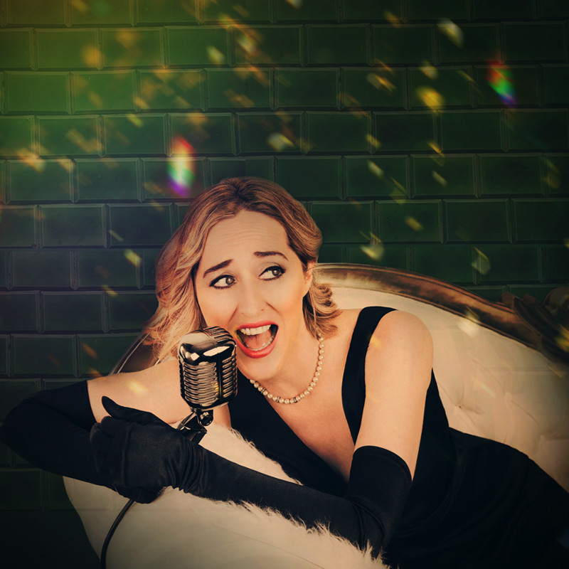Green Tile Tango - A photo of a woman with blonde hair sitting back on a chair while singing into a silver microphone. She is wearing a black dress with long black gloves. Blurred yellow lights feature across the image.