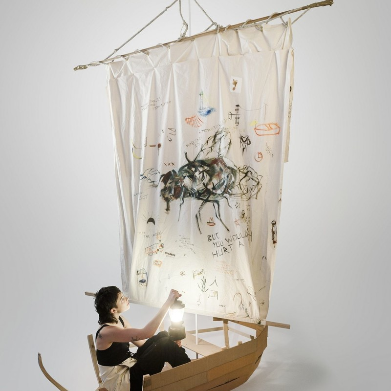 FELTspace Graduate Award Exhibition - Josie Dillon 'Small Chests' - A photo of a person sitting in a small wooden boat with a large white sail decorated with small drawings.