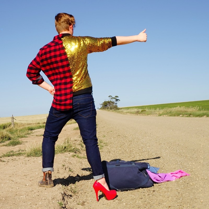 A photo of a person standing on the side of a deserted gravel road with one hand out with their thumb up. They are wearing a long sleeved shirt that is half black and red checked and half gold sequined. They are wearing dark blue denim jeans with one brown boot and one red high heel on.