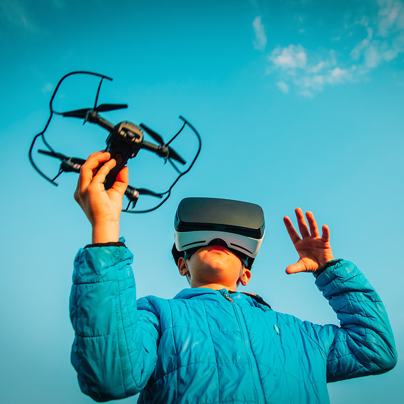 An image of a child holding a small black drone in one hand while wearing virtual reality goggles.