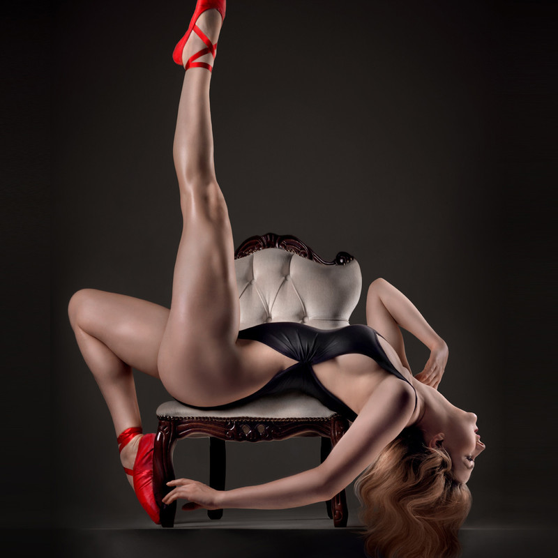 A woman with long blonde hair in a revealing black leotard is stretched in a back bend across a cream and wood, quilted arm chair. Her head is almost touching the ground, one leg is raised straight up in the air, the other is pointed towards the ground against the leg of the chair. She is wearing bright red ballet shoes with a ribbon around the ankles.