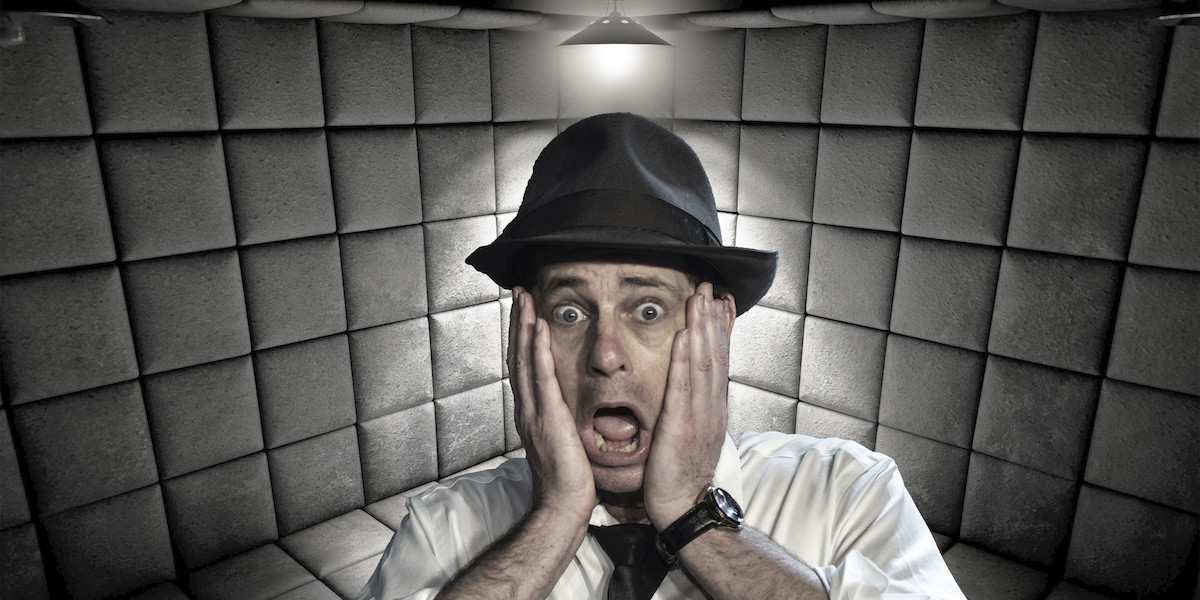A photograph of a man wearing a trilby hat and a long-sleeve white shirt. He has his hands placed on either side of his face expressing a shocked emotion. The background features a light grey quilted material and a small yellow light fixture above the man's head.