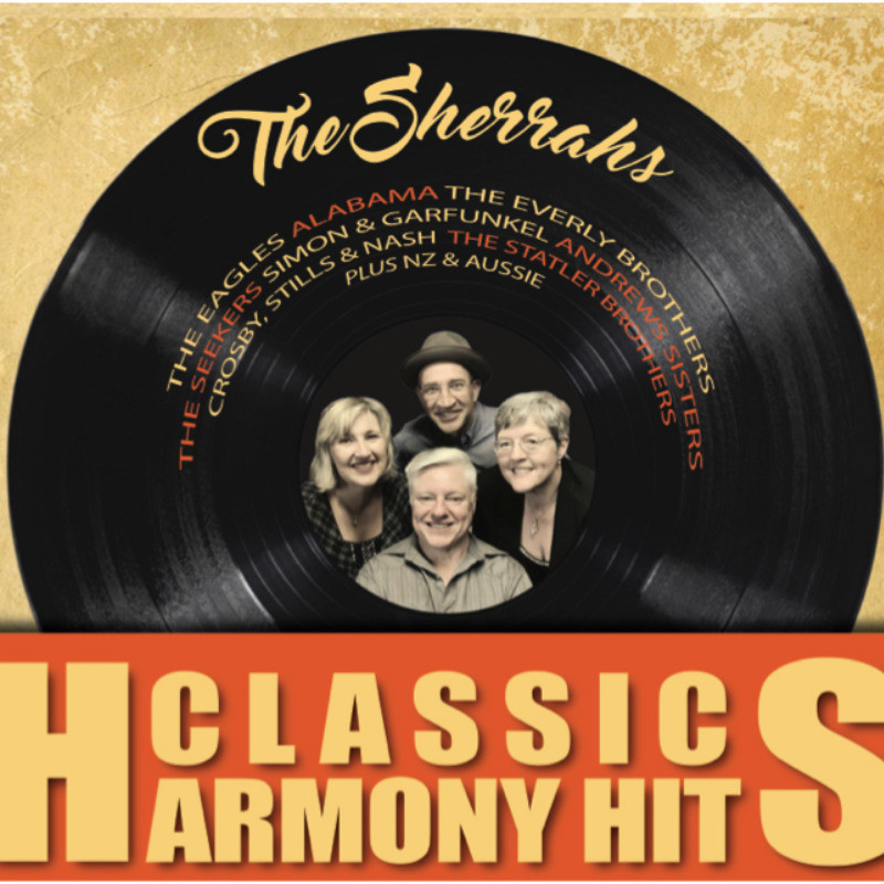 An image of a black vinyl record with a photo of four people smiling in the middle. There is text on the vinyl record that reads, 'The Sherrahs' in yellow calligraphy font. On the bottom of the image the text reads, 'Classic Harmony Hits' in yellow font within an orange banner.