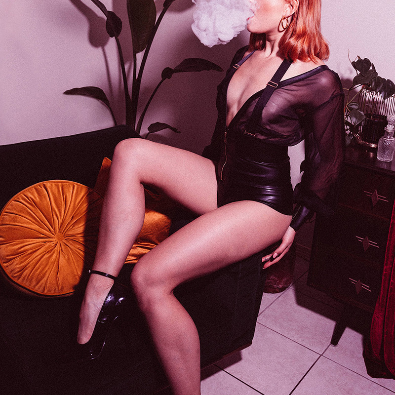 A woman in tight, black, leather, short shorts and a see through black blouse sits on the arm of a couch with one leg slightly raised. The top of her head is cropped out of the image, she has red shoulder length hair and she is blowing a thick plume of smoke out of her mouth. There is a mustard round cushion on the couch, a pot plant and a mid century chest of drawers in the background.