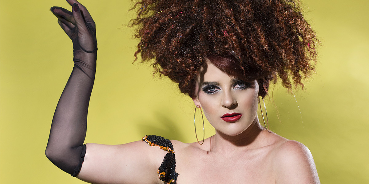 A photo of a woman that has fluffy brown hair tied up on top of her head. She is wearing a black mesh glove on one hand. The background is yellow.