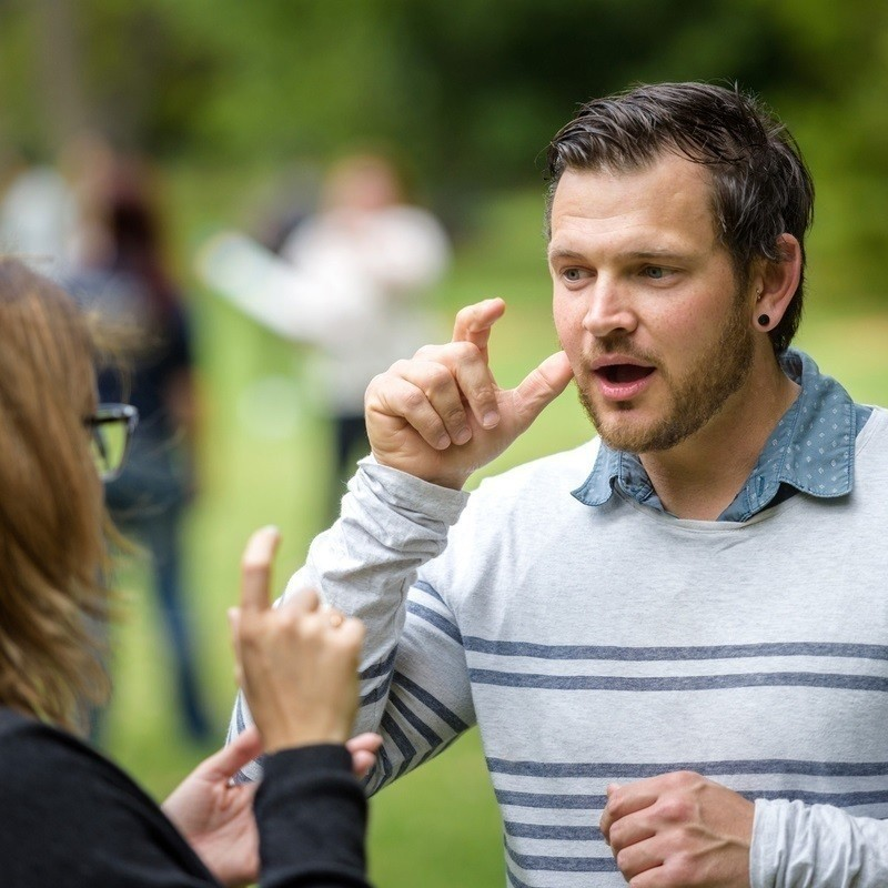 Come and Try Auslan with Deaf Can:Do - An image of a guy wearing a grey long sleeve striped t-shirt gesturing his hand to his cheek, to mirror a person teaching him Australian Sign Language (Auslan).