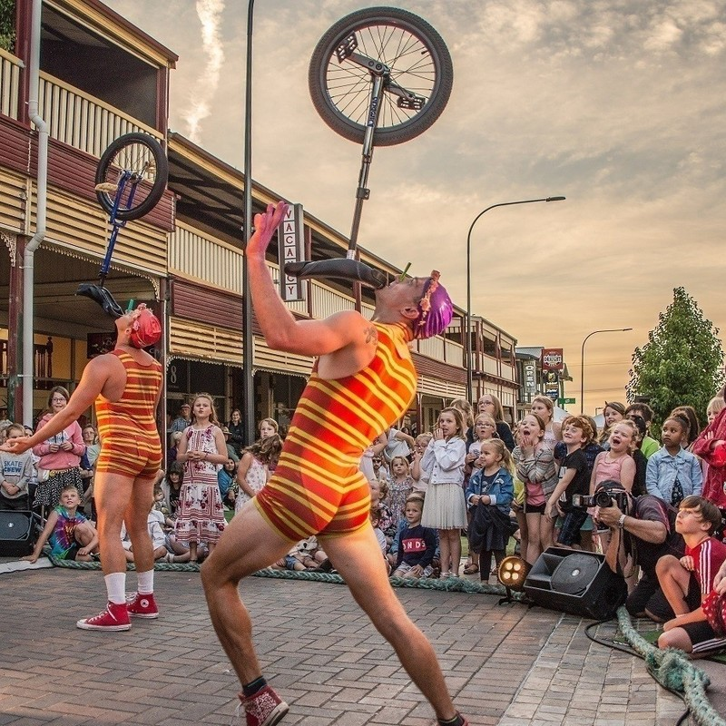 A photo of two performers wearing orange and yellow striped singlet's and shorts balancing unicycles on their chin. A group of children are eagerly watching the performance.