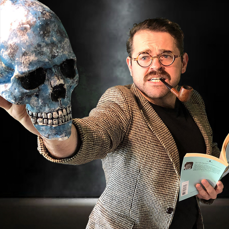 A photo of a man with a concerned expression on his face and a smoking pipe in his mouth. He is wearing brown tortoiseshell round framed glasses, black t-shirt and brown tweed jacket. He is holding a blue human skull in one hand and a book in the other.