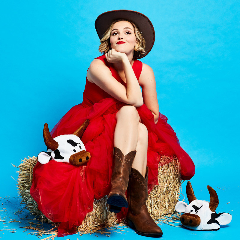 A woman sits with legs crossed on a hale bale. she is wearing cowboys boots and a cowboy hat. Her chin rests in the her hand. There are two plush cow toys on the ground.
