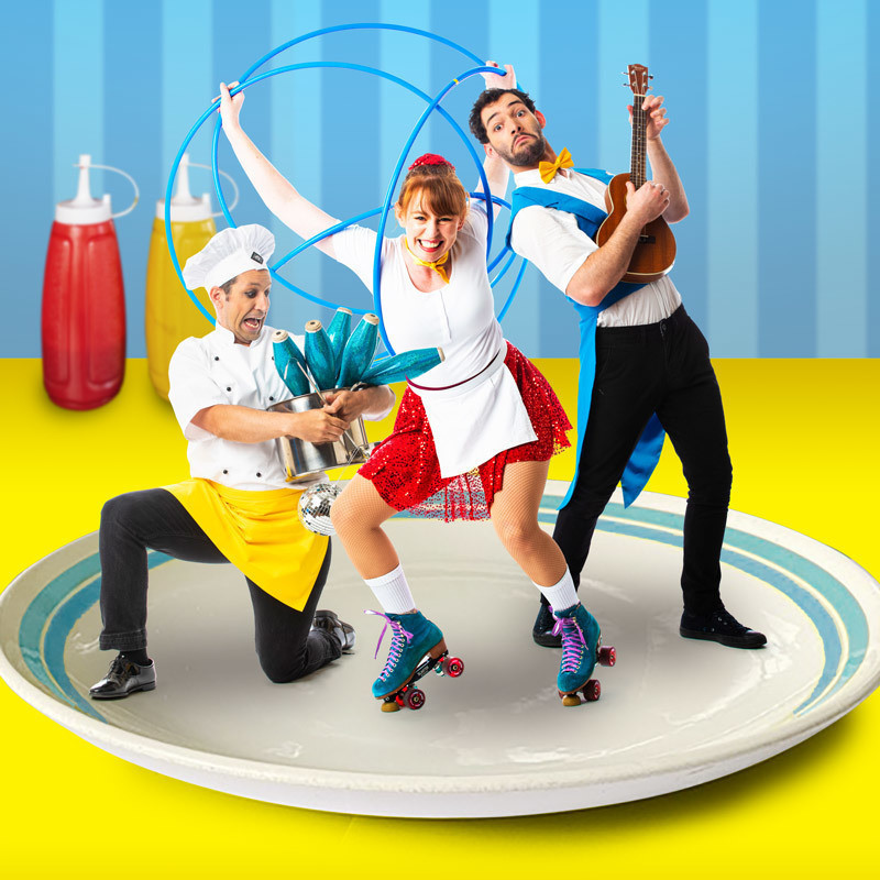An image of three people posing on a white plate. The person on the left is wearing a white chef's hat and is juggling batons in a silver pot. The person in the middle is wearing blue roller-skates and is holding three blue hula hoops above their head. The person on the right is holding a wooden ukulele.