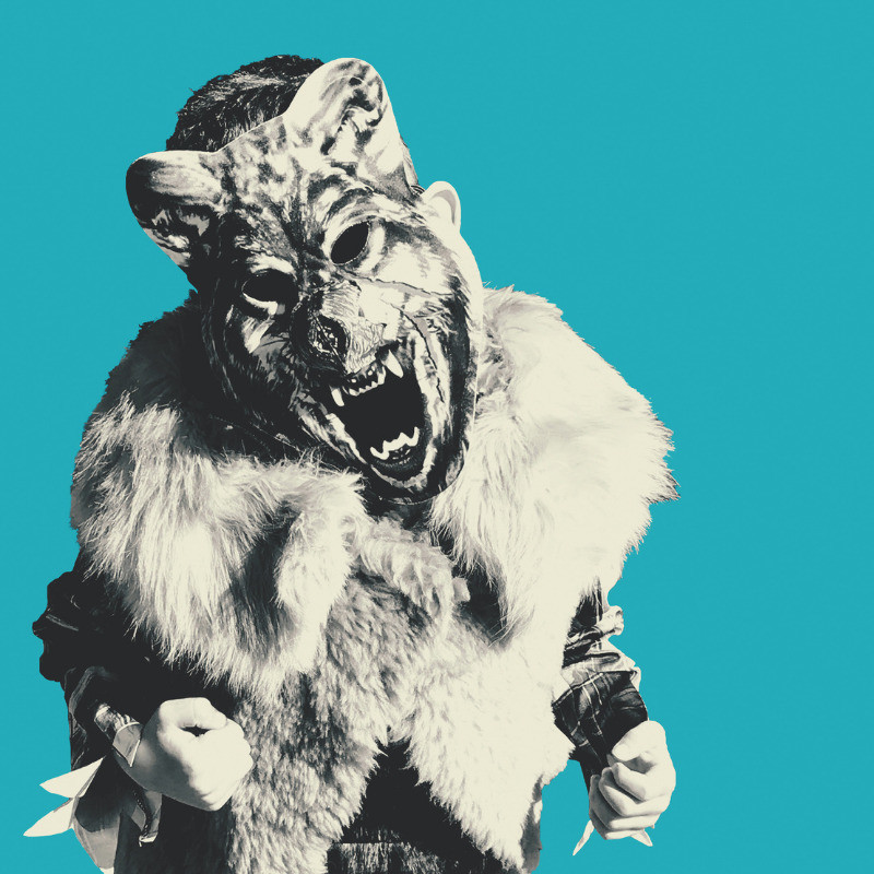 That Boy - A black and white photo of a person wearing an oversized fur jacket and a large detailed scary looking mask. The background of the image is blue.