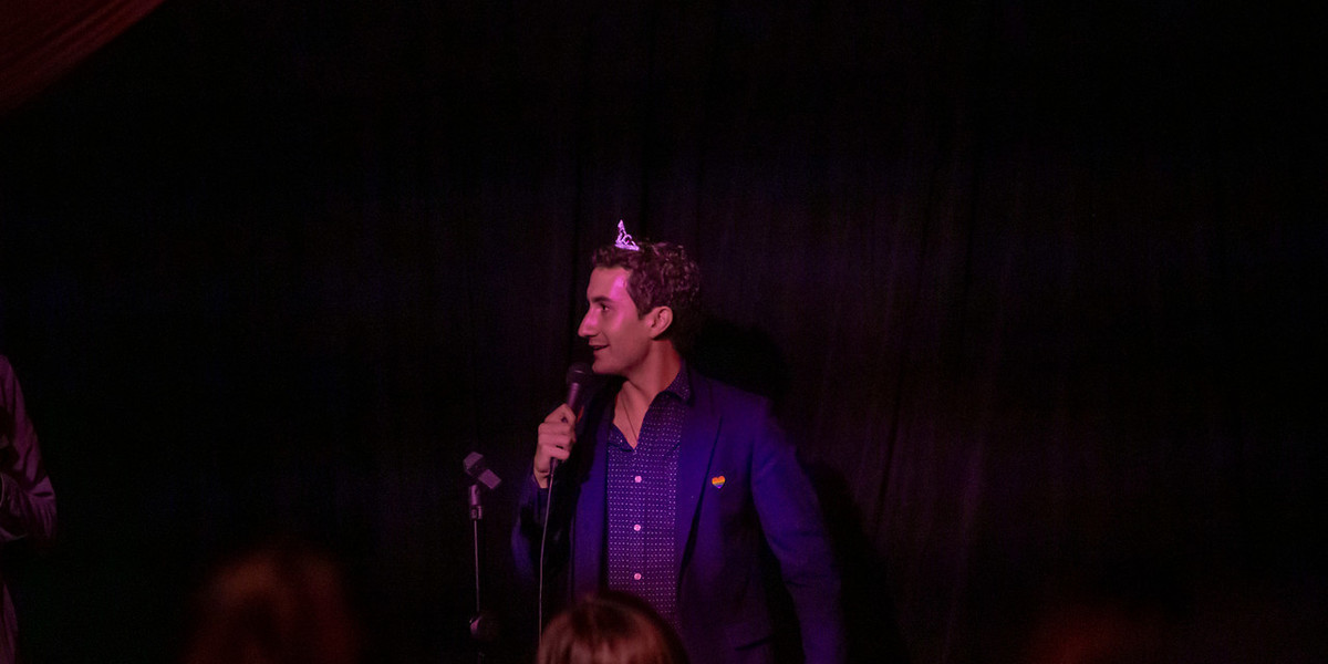 A photo of a man wearing a navy blue shirt and suit jacket as well as a silver tiara while standing in front of a black curtain that covers the background. He is holding a microphone and is gazing into the distance.