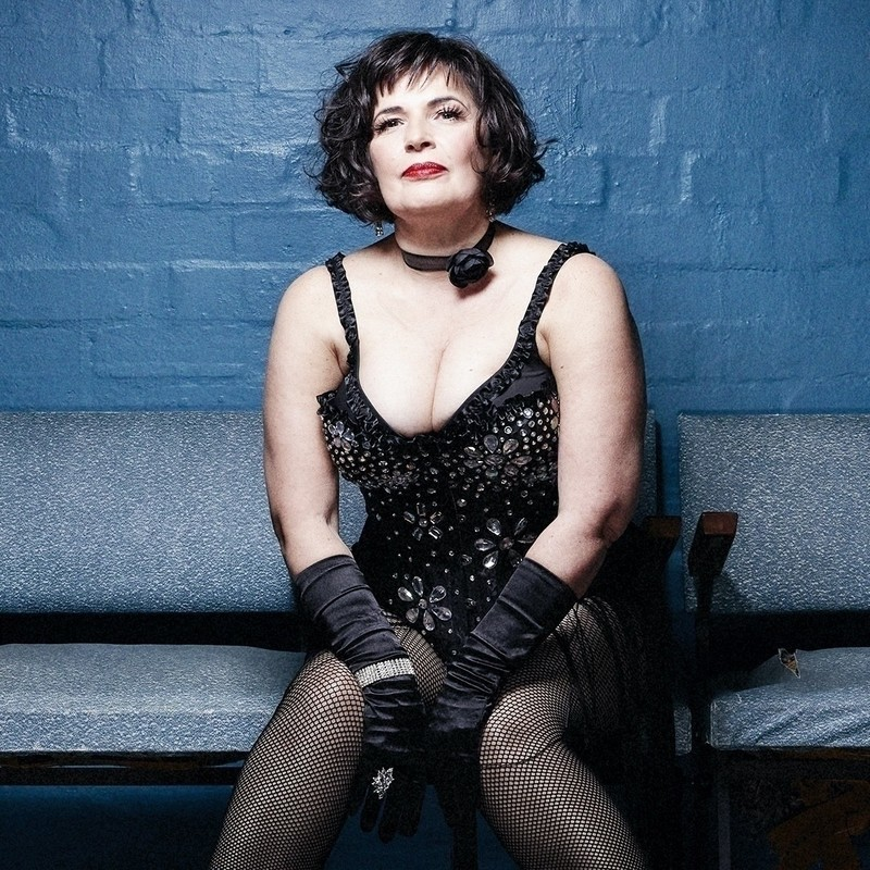 A fair skinned woman with dark brown hair just above shoulder length sits on a blue vinyl bench chair. She has bright red lipstick, a black choker, a low cut jewelled black leotard, fishnet stockings and elbow length gloves. There is a brick wall painted blue in the background.