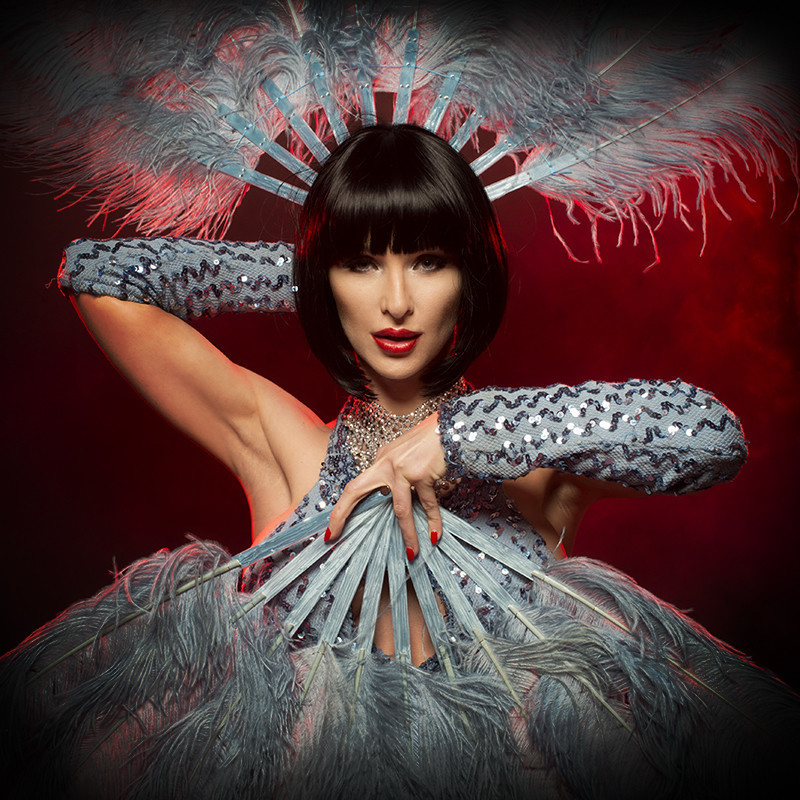 The Showgirl Experience - A photo of a person with short brown hair holding two feathered light blue hand fans, with one fanning around their head and the other in front of their chest. They have sparkly light blue gloves on.