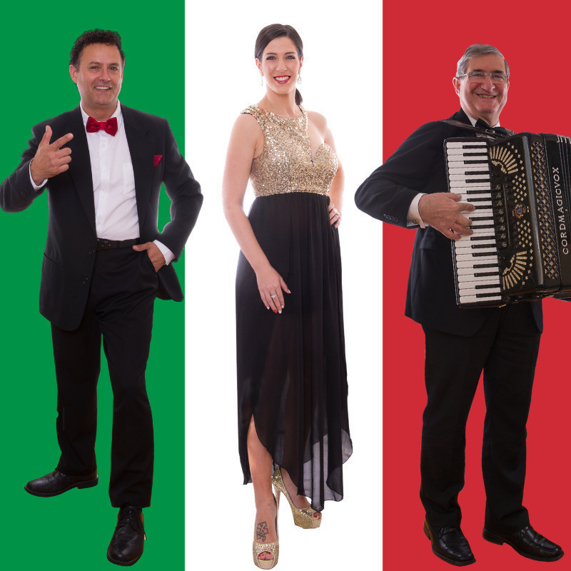 A photo of three people standing and smiling. The man on the left is wearing a black suit, white shirt and a red bow tie. The woman in the middle is wearing a gold top and black skirt with gold shoes. The man on the right is wearing a black suit and is holding an accordion in front of his body. The background is the Italian flag, which features a green, white and red stripe.