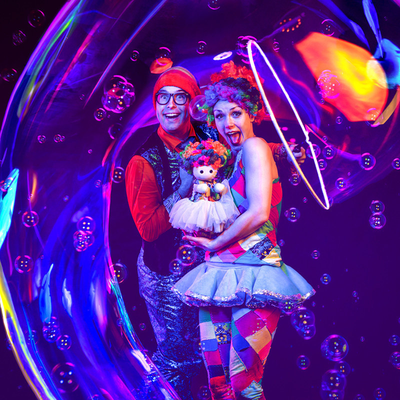 A photo of two people with excited facial expressions. They are both wearing multi-coloured outfits and the person on the right is holding a puppet. The background features lots of bubbles floating in the air around them.