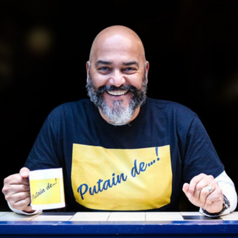 Talk Dirty, Stay Classy - A photo of a man smiling with his arms resting on a table. He is wearing a black t-shirt that has a yellow rectangle with blue cursive lettering inside it.