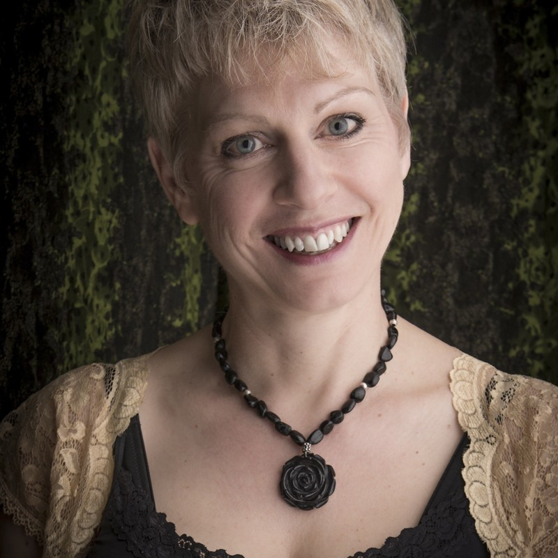 Household Names - A headshot of a smiling fair skinned woman with short blonde hair. The wears a cream lace bolero and a black necklace with a flower pendant.