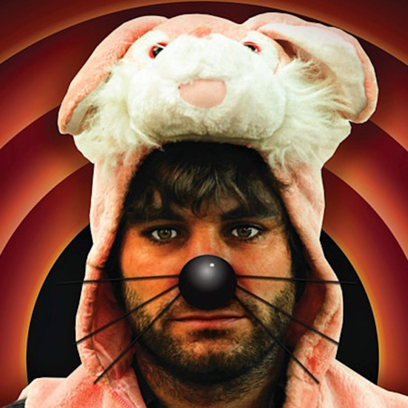 Jon Bennett: It's Rabbit Night!!! - The head of a man wearing a pink rabbit suit and a black nose with whiskers. He has brown hair and brown stubble. The background is a concentric orangey-pink circles.