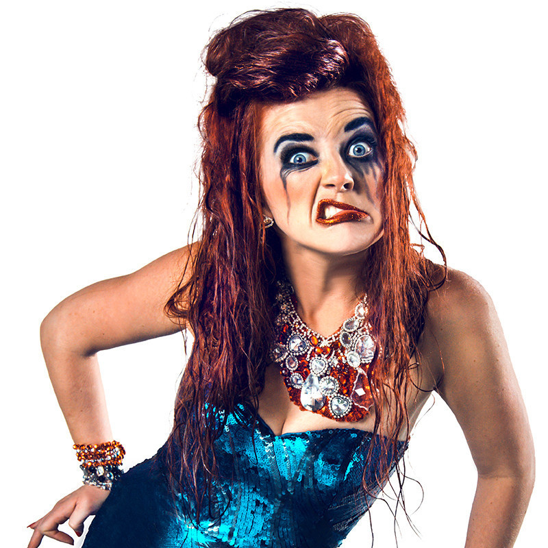 A photo of a woman wearing a blue sequined gown and an orange necklace with silver embellishments. The woman also has red hair that appears to be wet. She has black eye makeup running down her face and a disgruntled look on her face.