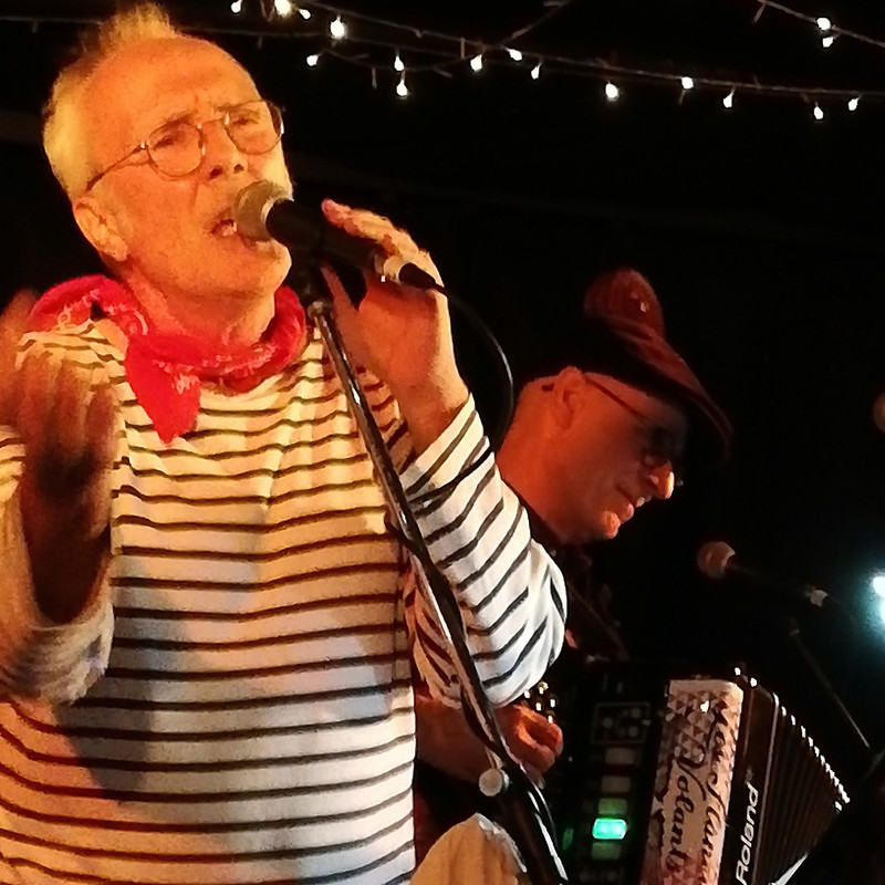 Jacques is Bacque - A man wearing glasses, a red bandana scarf and a blue and white striped long sleeve shirt sings into a microphone on a stand. A man in the background wears a black flat cap and plays the accordion.