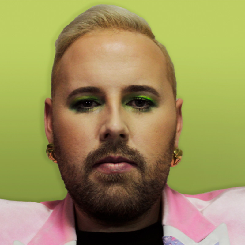A headshot photo of a person with short blonde hair and a brown beard. They have bright green eyeshadow on their eyelids and gold earrings in their ears.