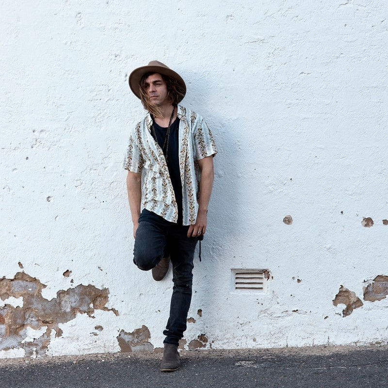 A photo of a person leaning against a white wall. The person is wearing a brown hat, black t-shirt, black jeans and a patterned white shirt.