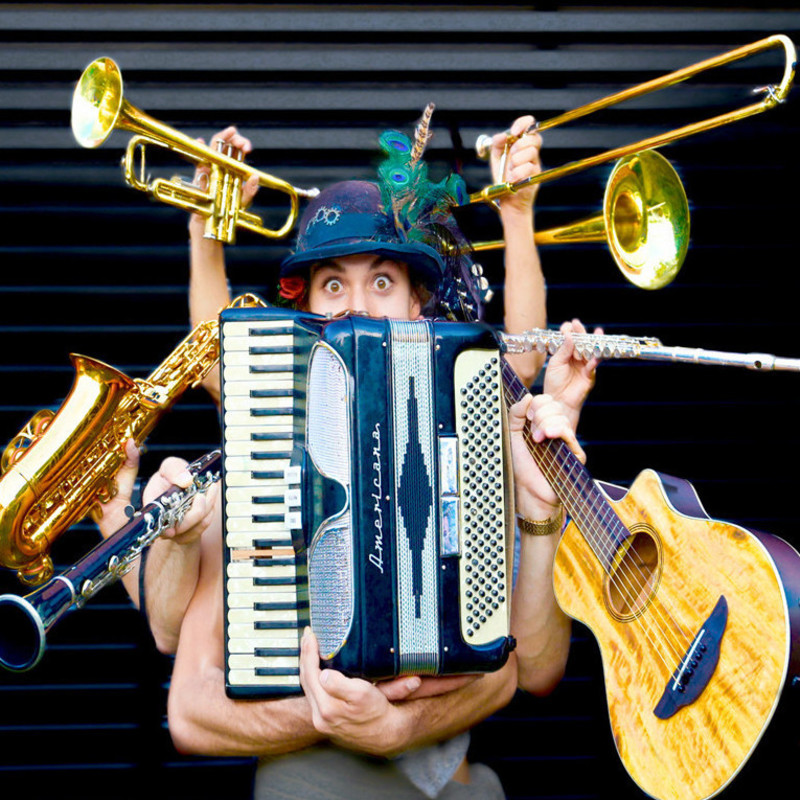 Musical Improv - The Immature Amateurs - An photo of a person holding an accordion in the middle of the image with other hands holding a trumpet, saxophone, clarinet, trombone, flute and guitar around the middle.