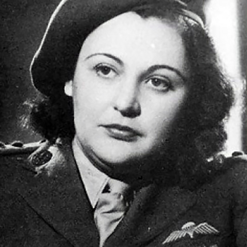 The White Mouse - A black and white photo of Dame Nancy Wake, who was a leader in World War 2. In the photo she has a serious expression on her face and is wearing a beret on the side of her head with a jacket, shirt and tie. She has short black curly hair.