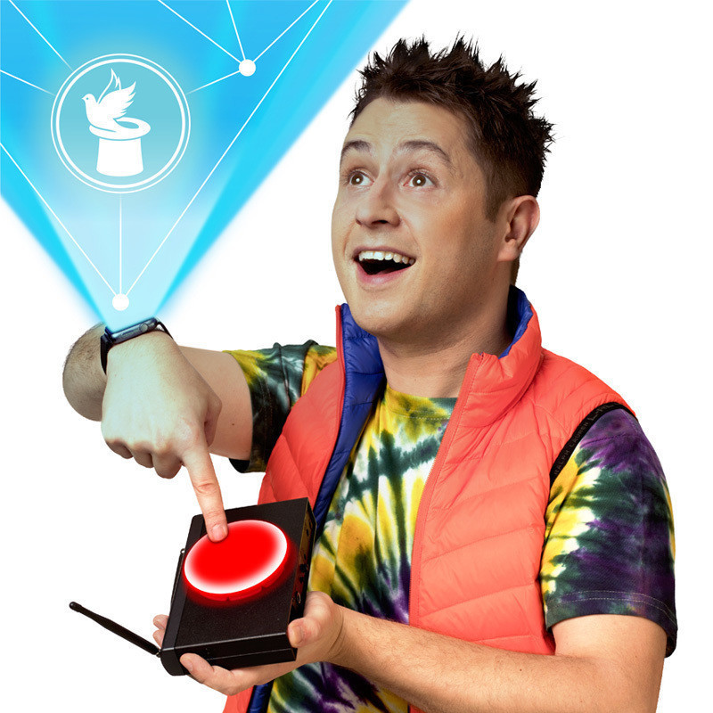 Mickster's Magic Gadgets: Reloaded - A photo of a guy wearing a yellow, green and purple tie die t-shirt with an orange vest. In one hand he is holding a black gadget that has a red button and is pressing the button with the other hand. A blue stream of light has been illustrated coming out of his watch. Inside the blue stream is a white top hat with a bird coming out of it.