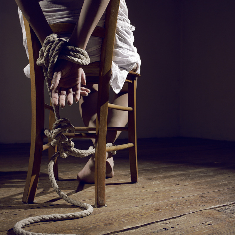 CHAIR CHAINED - A photo of a person sitting a wooden chair with their hands tied together behind them with a beige rope.