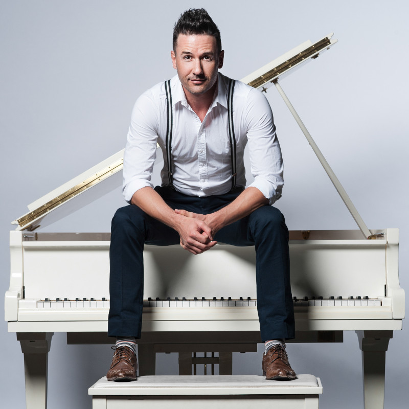 Michael Griffiths: Greatest Hits - A photograph of a man sitting on top of a white piano. He is wearing a white shirt, blue pants, with black suspenders and brown shoes.