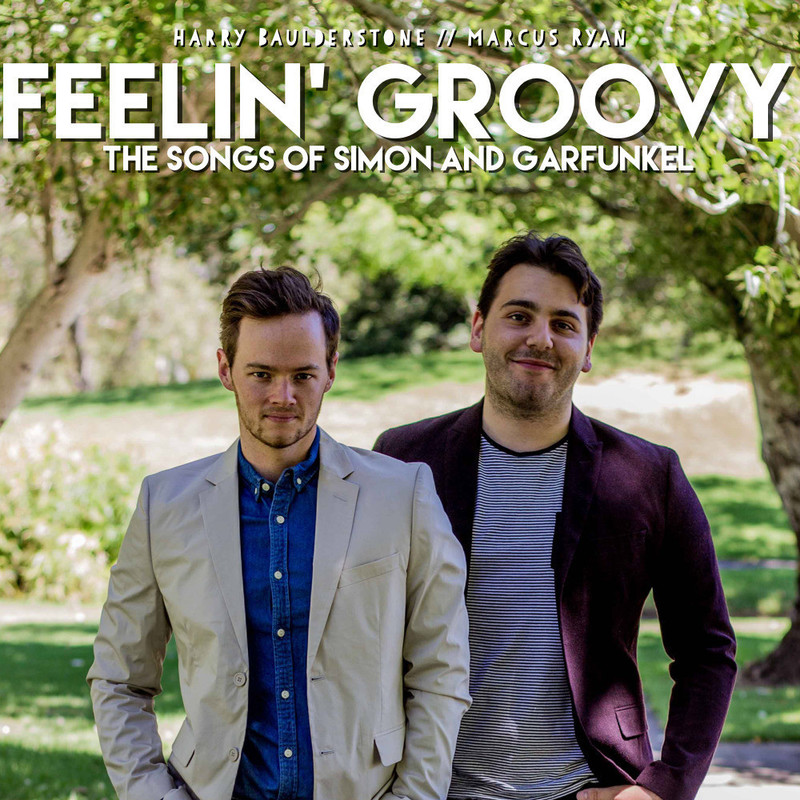 """Feelin' Groovy - The Songs Of Simon & Garfunkel - Two men stand in a park surrounded by trees and grass. White text across the top reads """"Harry Baulderstone //Marcus Ryan, Feelin' Groovy, the songs of Simon and Garfunkle"""". Both men have fair skin, short dark hair and dark stubble. The man on the left wears a beige blazer and denim shirt, the one on the right wears a purple blazer and a black and white striped t-shirt."""