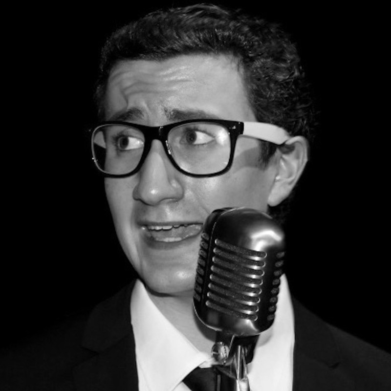 A black and white photograph of a person wearing glasses singing into a silver microphone.