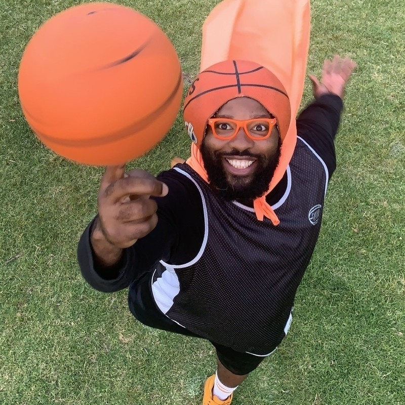 BasketballMan Can Fly - A photograph taken from a bird's eye view of a man balancing a basketball on his finger. The man is dressed in all black clothing ad has a bright orange cape on. He has cut a basketball to wear it as a hat, as well as wearing orange framed glasses on his face. He has a wide grin on his face. The background is green grass.