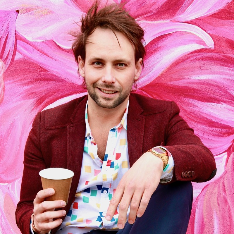Rich Jay: Being Rich but Dying Trying - A photo of a smiling man wearing a maroon jacket, white shirt with multicoloured squares. He is also holding a brown cup and is wearing a gold watch. The background is painted with pink and red.