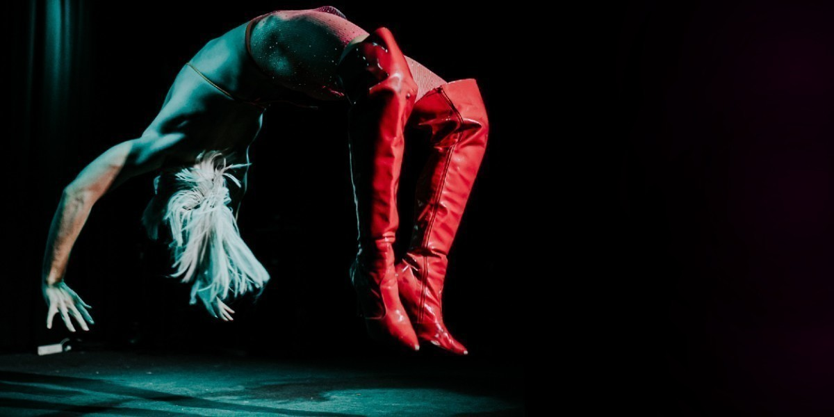 A photograph of a person in the process of performing a backflip. They have blonde hair and a wearing knee-high red boots.