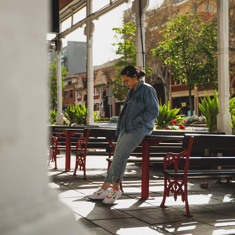 My Story - A photo of a young woman leaning on a table and looking down at the ground. She is wearing a denim jacket and denim jeans with white sneakers. The background features trees and historic looking buildings.