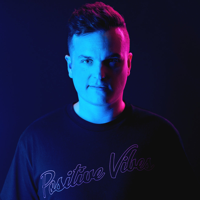 Matt Tarrant: HAPPY - A photo of a man with a smirk on his face wearing a black shirt that says 'Positive Vibes'. His face is illuminated with blue and red light.