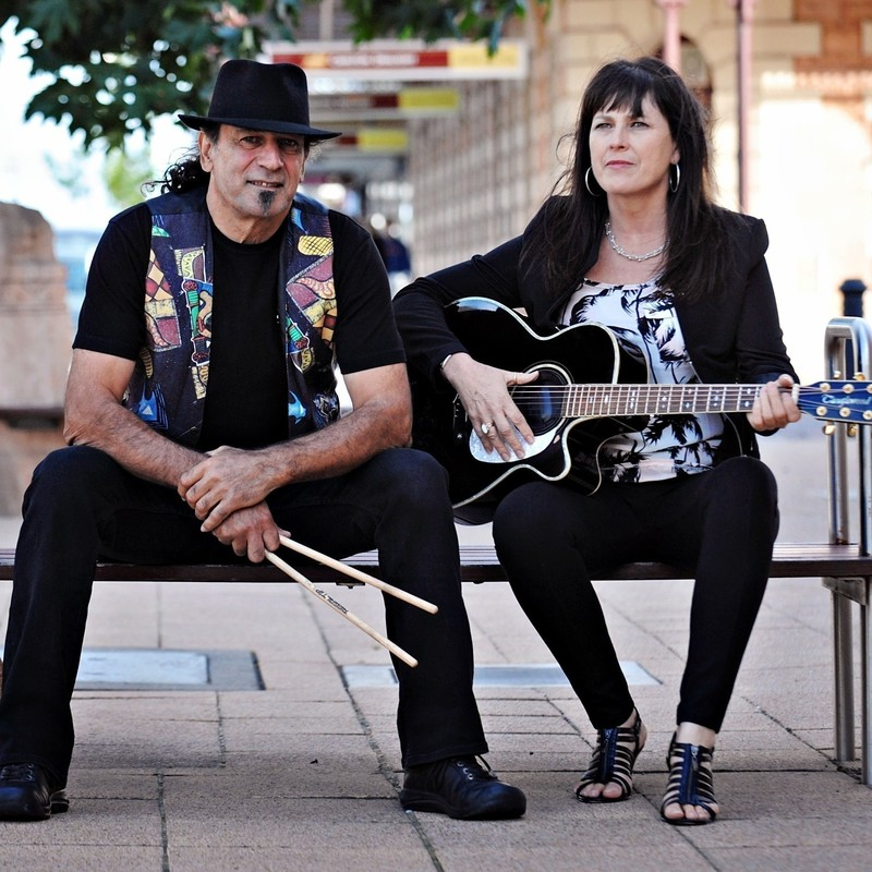 A man and a woman sit on a bench, the man wears a colourful waistcoat, black t-shirt, black hat and black jeans. His forearms lean on his thighs and he hold drumsticks. The woman wears a black jacket, black pants, a black and white blouse and holds a black and white acoustic guitar.