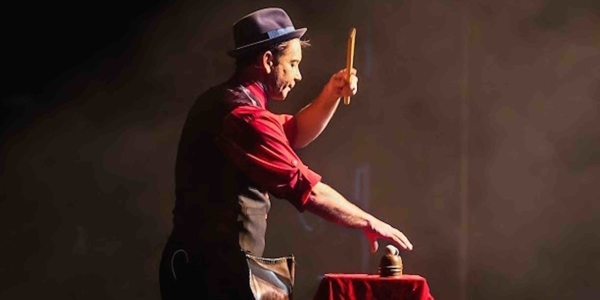 Man wearing a red shirt, a black waist coat and black hat performing magic trick.